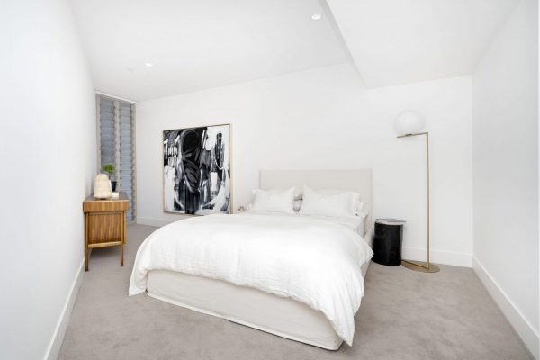 Large bedroom with bed and white sheets